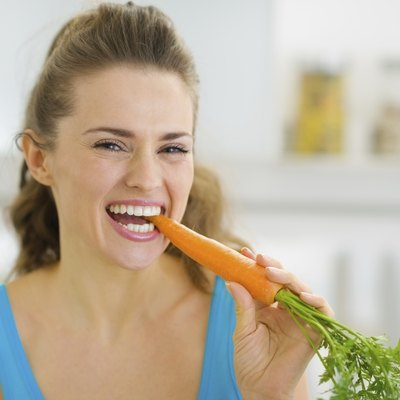 Happy young woman eating carrot in kitchen