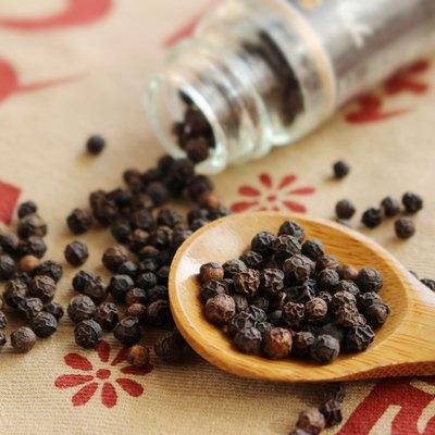 Black pepper seeds spills out of bottle