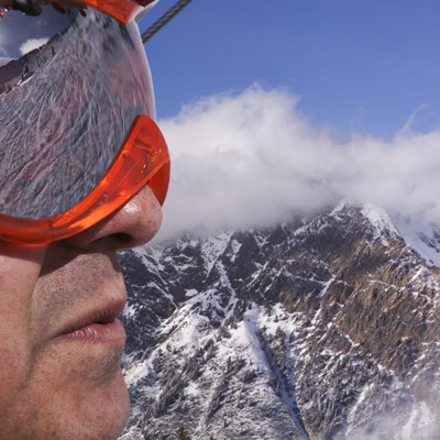 portrait of a male skier in goggles overlooking the snow covered mountains