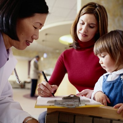 Mother with daughter (1-3) signing form for pediatrician