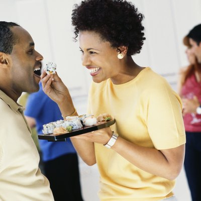 African woman feeding husband sushi