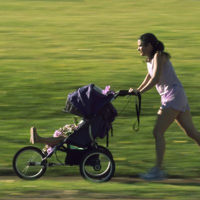 Mother Jogging In The Park With Her Baby In A Stroller