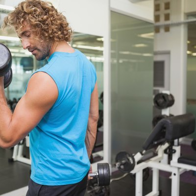 Handsome young man exercising with dumbbell in gym