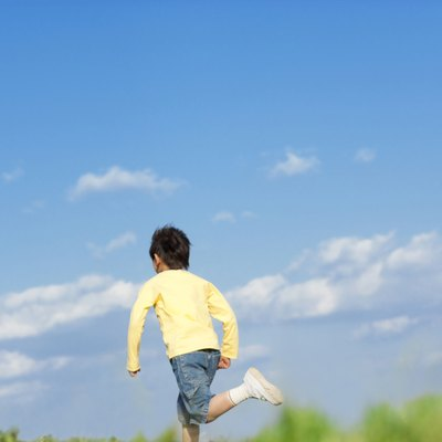 Rear view of young boy running against a blue sky
