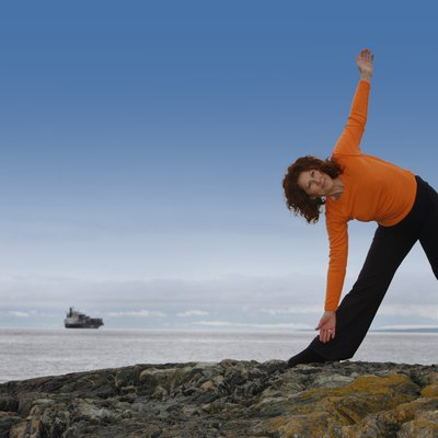 Woman stretching on a rocky beach