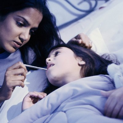 portrait of mother taking daughters temperature