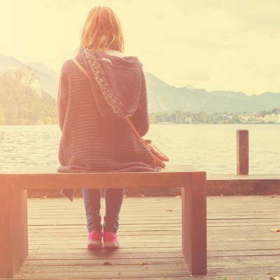 Girl sitting on a wooden pier near water.