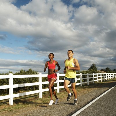Man and woman jogging along country road