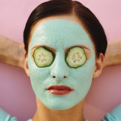 woman lying down with a face pack and cucumber slices