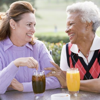 Two Female Friends Enjoying Beverage By A Golf Course