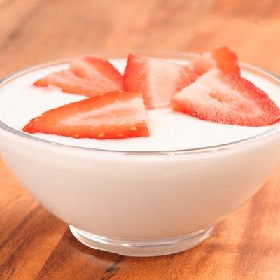 full bowl of yogurt with strawberries on wood