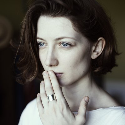 Portrait of a woman holding her hand to her mouth