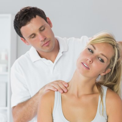 Handsome physiotherapist examining patients neck