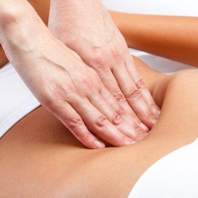 Therapist Hands pressing on female abdomen.