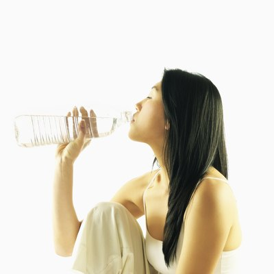 Side profile of a young woman drinking water