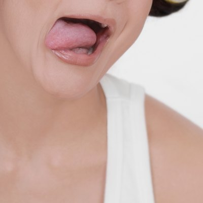 Young woman sticking her tongue out, close-up, part of