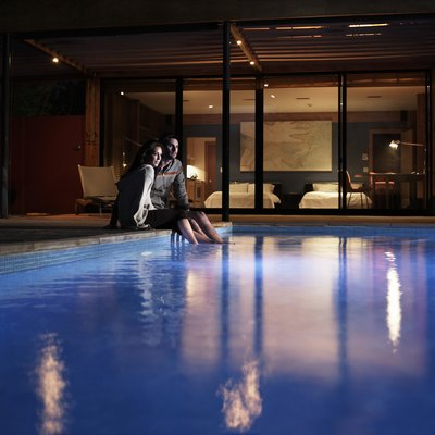 Young couple sitting at edge of pool at night