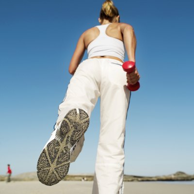 low angle view of a woman working out with dumbbells on the beach