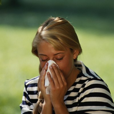 Young woman blowing nose, eyes closed, outdoors