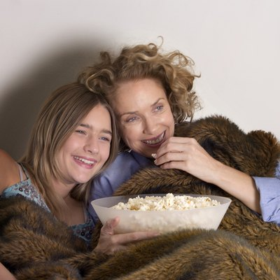 Mother and daughter (13-15) on sofa sharing popcorn, laughing