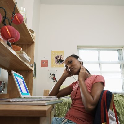 Young woman sitting at desk, wearing headphones, in student dormitory