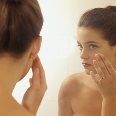 Young woman in bathroom, doing make up in front of mirror, close-up