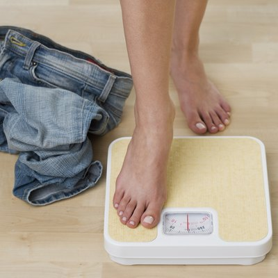 Woman stepping on scale, low section, close-up