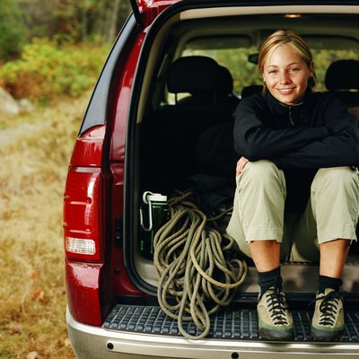 Femal rock climer sitting with gear in back of SUV, portrait