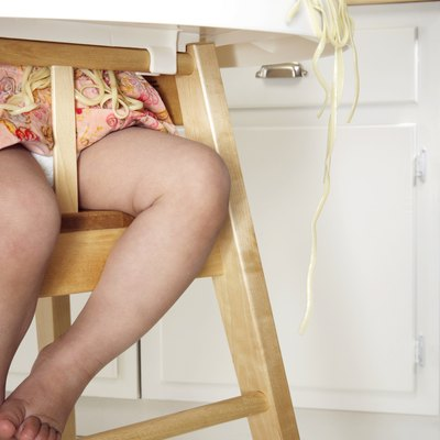 Baby girl (18-24 months) in high chair, spaghetti hanging over tray