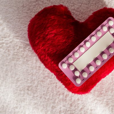 Oral contraceptive pills on red heart
