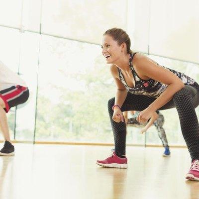 Smiling woman squatting in aerobics class