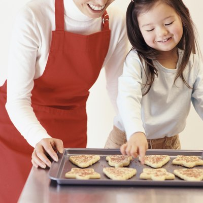 Young Girl Stands With Her Mum by the Kitchen Counter, Choosing a Christmas Cookie From a Baking Tray