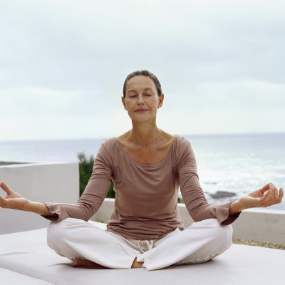 Senior Woman Meditating in the Lotus Position with the Sea in the Background