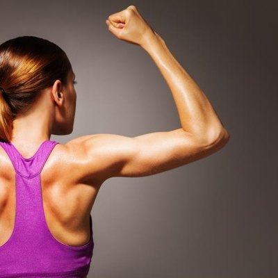 Strong hands back and shoulder of fit young woman who exercise, dramatic portrait