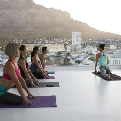 Yoga class practicing in huge rooftop studio at sunset