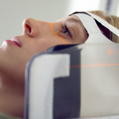 close up of a blonde caucasian female patient as her head is strapped into a cat scan machine