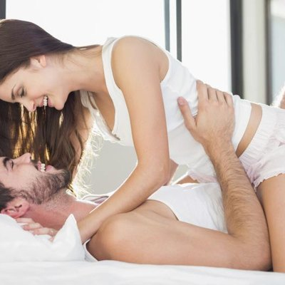 Young couple having fun in bed at home in bedroom