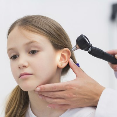 General practitioner auscultating the ear of a patient