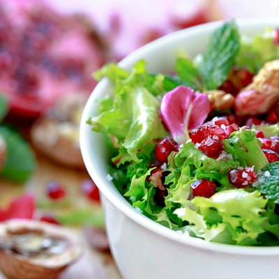 Curly endive salad with pomegranate, nuts, rose petals...