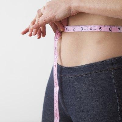 Caucasian woman measuring her waistline