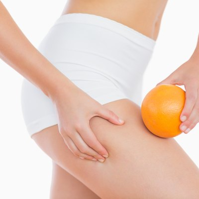 Woman squeezing fat on thigh as she holds orange
