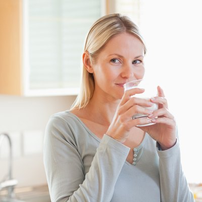 Woman standing in the kitchen drinking some water