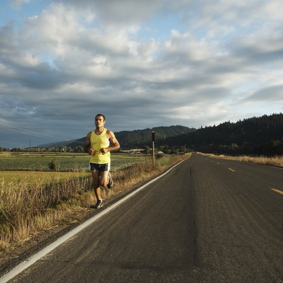 Male jogging by road in rural landscape
