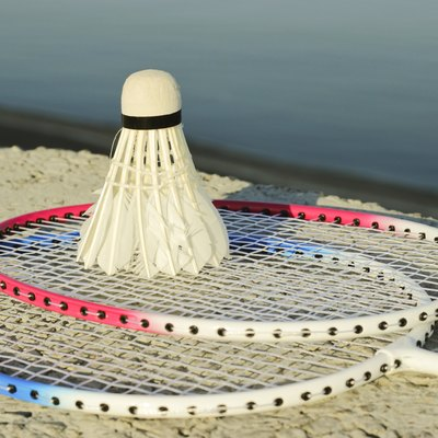 Badminton racquets with shuttlecock on a stone bench against the