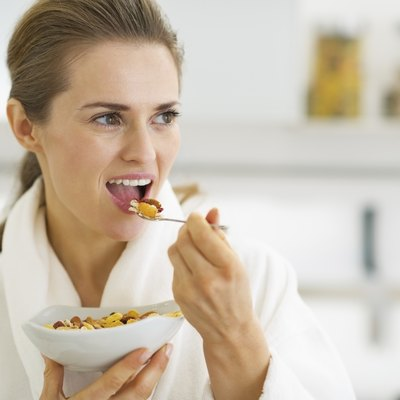 Young housewife having healthy breakfast in kitchen