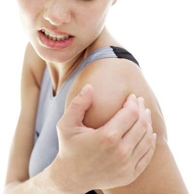 young woman holding her shoulder in pain