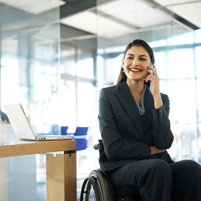 businesswoman sitting in a wheelchair talking on her mobile phone
