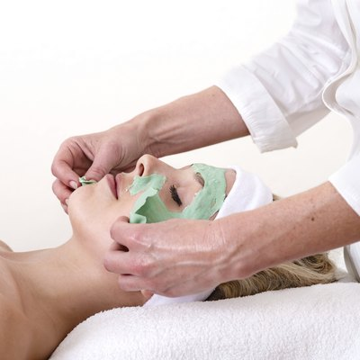 Beautician peeling off a green thalasso beauty facial mask.