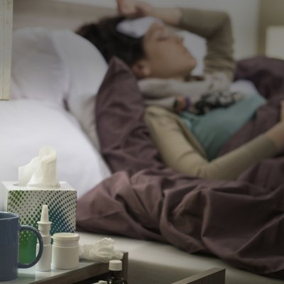 Tissue, flu medicines ill woman bedside table