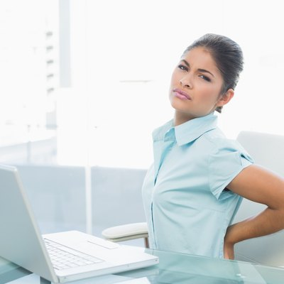 Businesswoman suffering from back ache in office